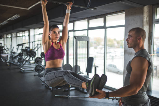 woman doing abs workout on horizontal bar with personal trainer - horizontal bar stock photos and pictures
