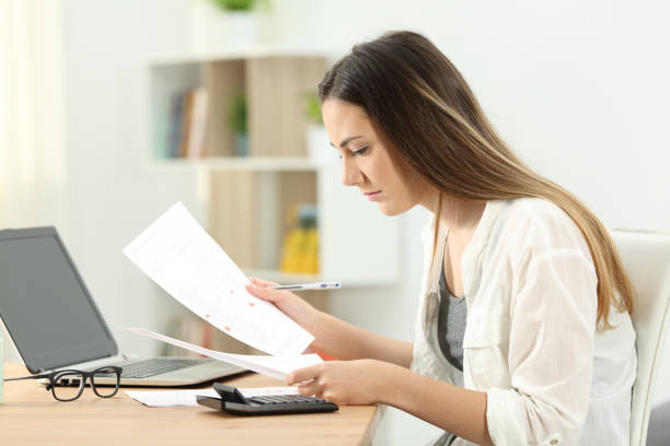 Woman doing accounting comparing documents stock photo