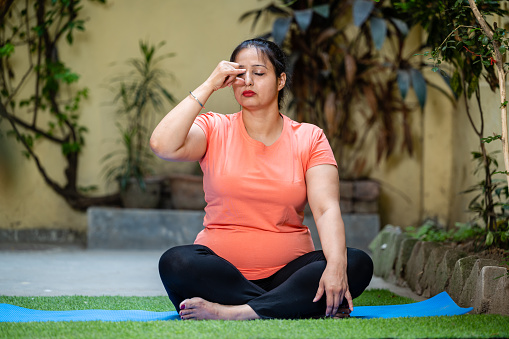 Beautiful young woman in sports wear doing Anulom Vilom (Yoga Position) at of her yoga studio outdoor in day time. Inhaling and exhaling practice or Breathing exercise.