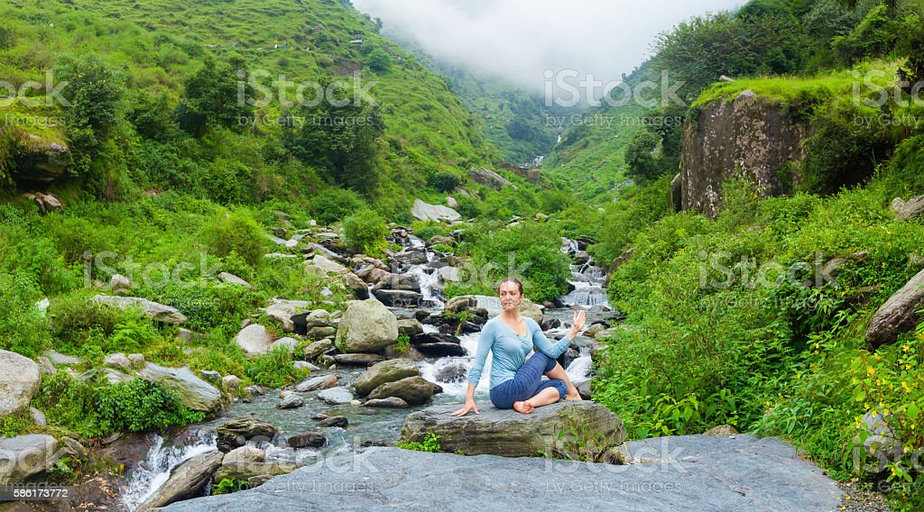 Woman doing Ardha matsyendrasanaasana asana outdoors stock photo