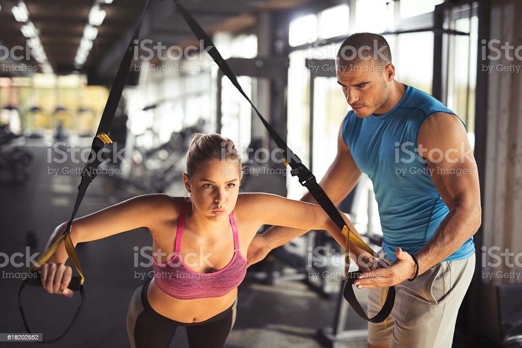 Woman doing arm exercises with suspension straps at gym. - foto de stock