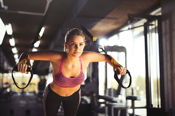 Woman doing arm exercises with suspension straps at gym. – Foto