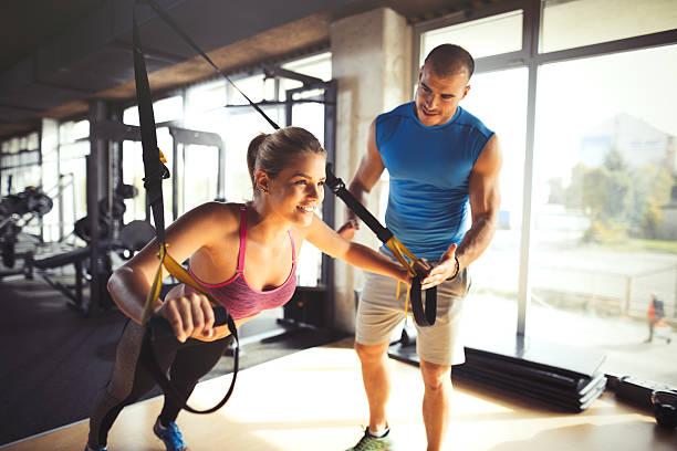 woman doing arm exercises with suspension straps at gym. - entrenador personal fotografías e imágenes de stock
