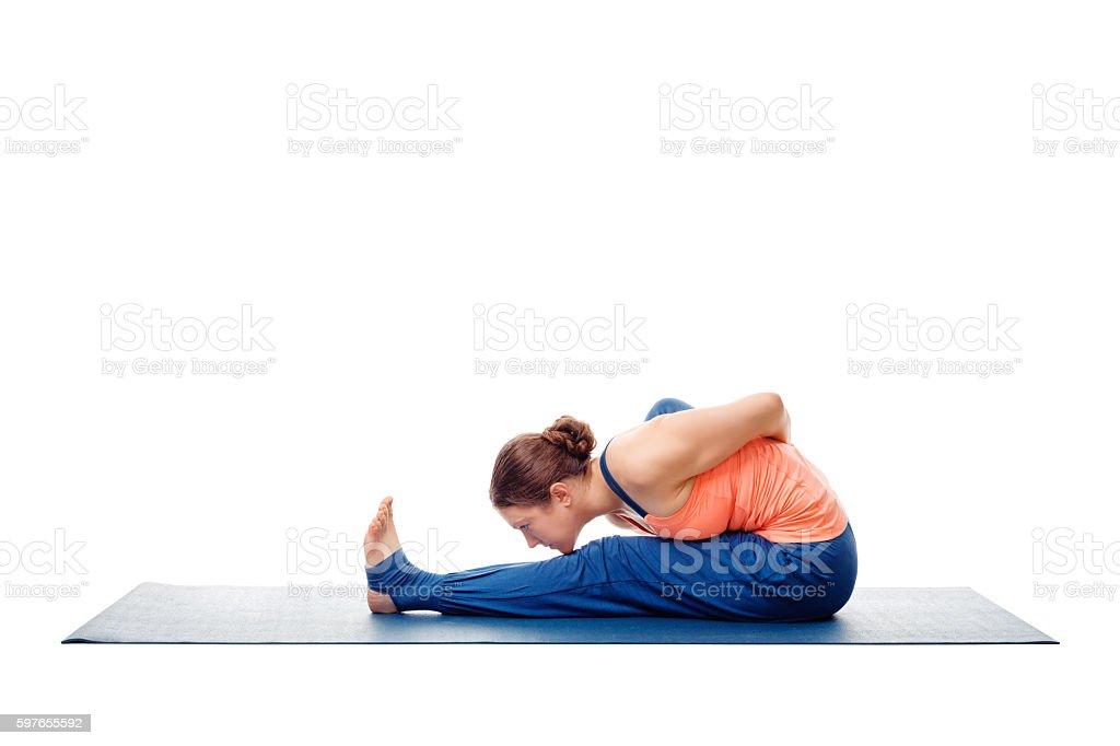 Woman doing Ashtanga Vinyasa Yoga asana Marichyasana A isolated stock photo