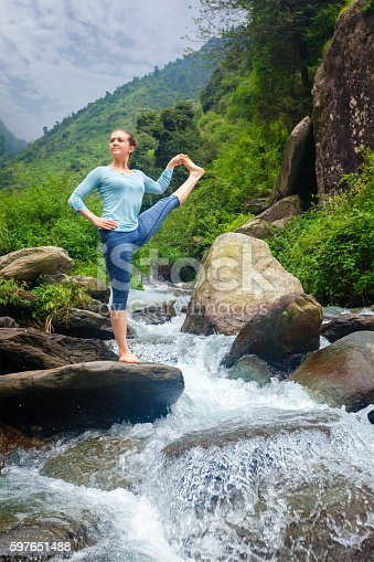 Yoga outdoors - woman doing Ashtanga Vinyasa Yoga balance asana Utthita Hasta Padangushthasana - Extended Hand-To-Big-Toe Pose position posture outdoors at waterfall