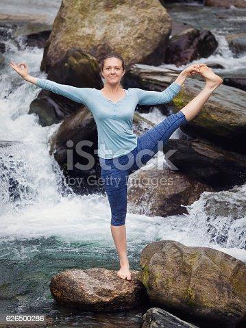 Yoga outdoors - woman doing Ashtanga Vinyasa Yoga balance asana Utthita Hasta Padangushthasana - Extended Hand-To-Big-Toe Pose position posture outdoors at waterfall. Vintage retro effect filtered hipster style image.