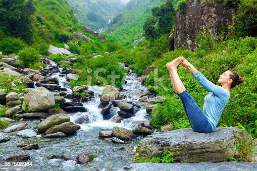 Yoga exercise outdoors - panorama of woman doing Ashtanga Vinyasa Yoga balance asana Ubhaya padangusthasana Big Double Toe Yoga Pose at tropical waterfall in Himalayas in India. Panoramic image