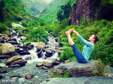 Yoga exercise outdoors -  panorama of woman doing Ashtanga Vinyasa Yoga balance asana Ubhaya padangusthasana Big Double Toe Yoga Pose at tropical waterfall in Himalayas in India. Panoramic image. Vintage retro effect filtered hipster style image.