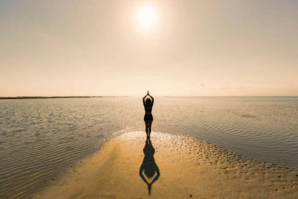 Woman doing at yoga at the sea Woman doing yoga sun salutation at the sea sun salutation stock pictures, royalty-free photos & images