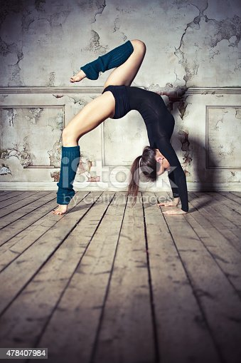 Young woman doing bridge stand with knee raised in the vintage interior