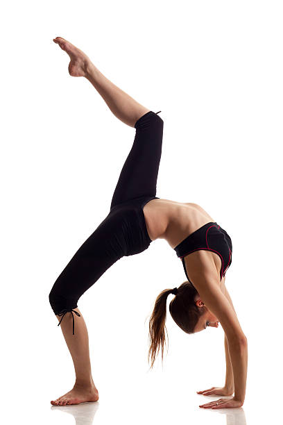 Woman doing back-bend with knee raised Gymnast girl do a back-bend on white background bending over backwards stock pictures, royalty-free photos & images