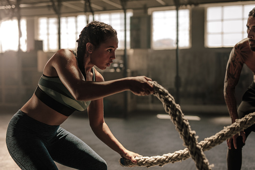 Powerful muscular woman exercising with battle ropes at the gym with personal trainer. Battle rope workout at gym with instructor.