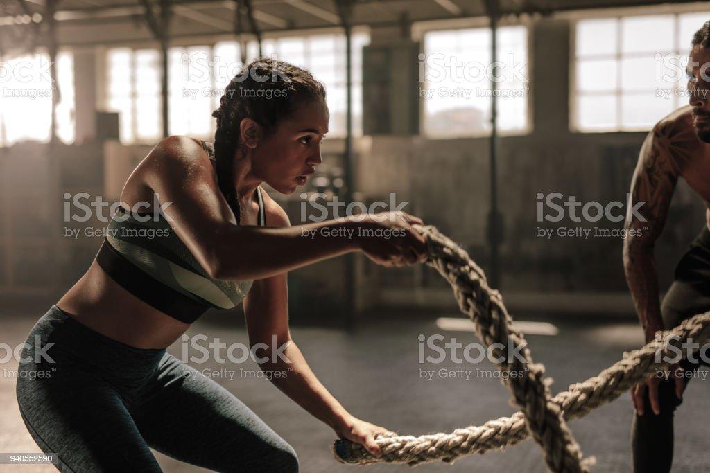 Femme faisant bataille corde séance d'entraînement au gymnase - Photo