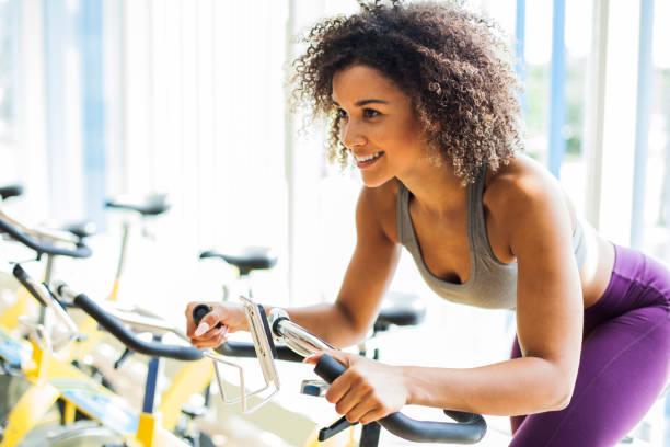 vrouw doen cardio oefeningen op een upright bike in de sportschool - ronddraaien stockfoto's en -beelden