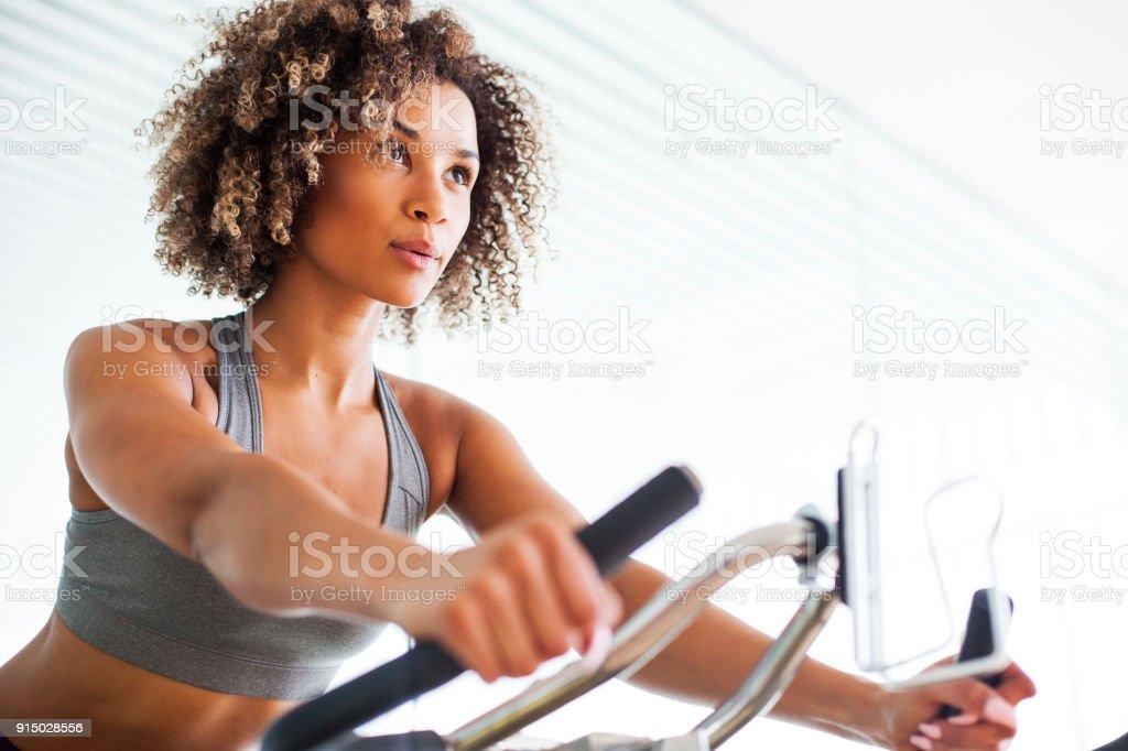 Woman Doing Cardio-Übungen auf einem stationären Fahrrad in der Turnhalle – Foto