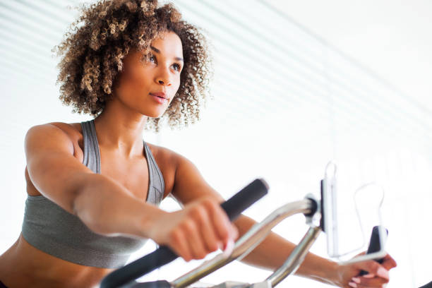 Woman Doing Cardio Exercises on a Stationary Bike at the Gym Woman Doing Cardio Exercises on a Stationary Bike at the Gym exercise bike stock pictures, royalty-free photos & images