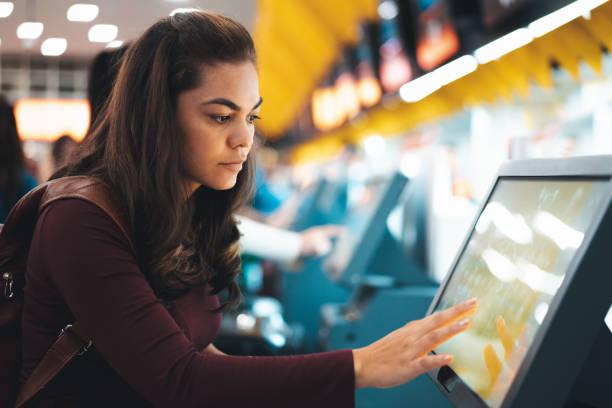 femme effectuant l'enregistrement pour le vol à l'aéroport - écran tactile photos et images de collection