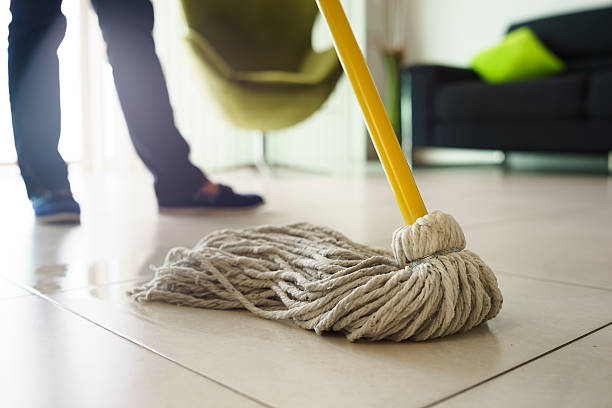 Woman Doing Chores Cleaning Floor At Home Focus on Mop stock photo