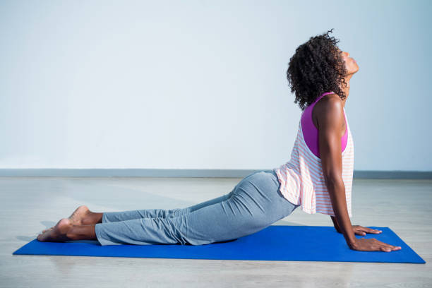 Woman doing cobra pose on exercise mat Woman doing cobra pose on exercise mat in gym cobra pose stock pictures, royalty-free photos & images