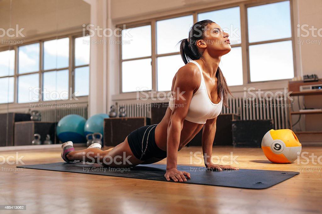 Woman doing core stretch in gym stock photo