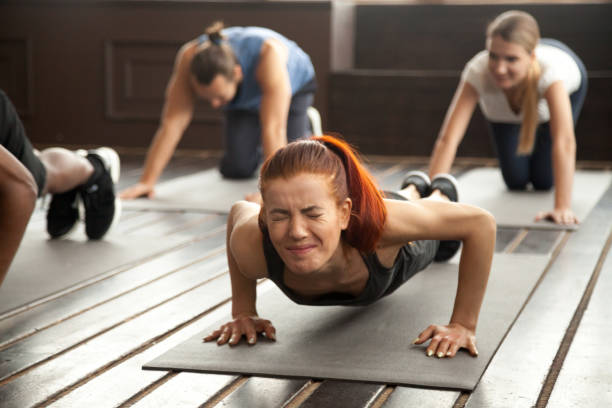 Woman doing difficult plank exercise or pushups at group training Young fit sporty woman with painful face expression doing hard difficult plank fitness exercise or push press ups feeling pain in muscles at diverse group training class in gym, endurance concept passion stock pictures, royalty-free photos & images