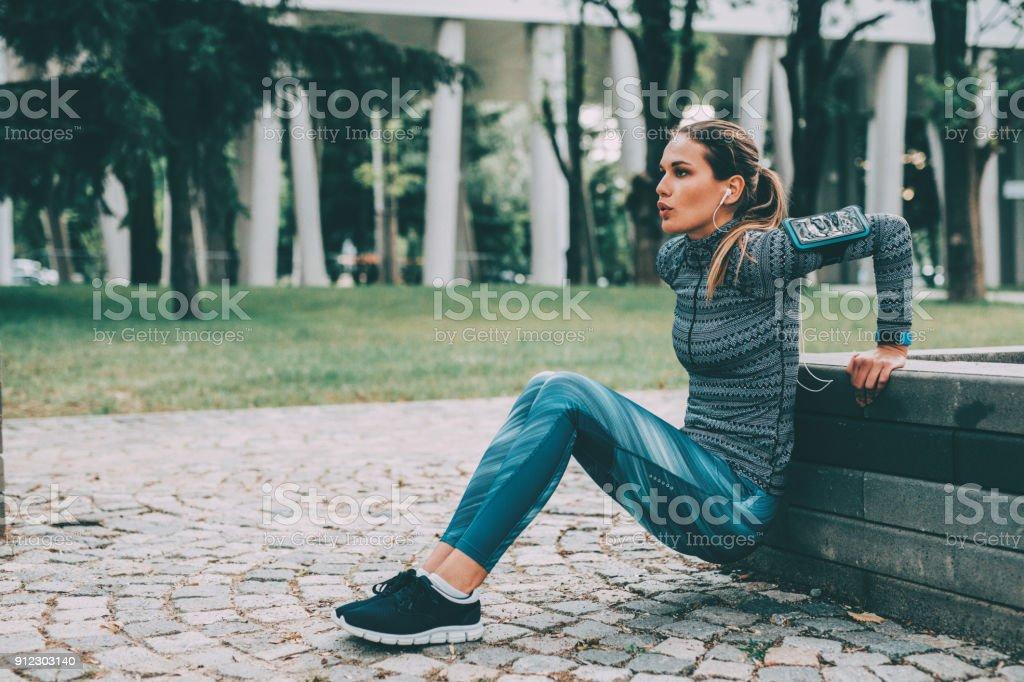 Woman doing dips outdoors stock photo