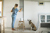 Woman painting with paint roller, she is dedicated and determined to finish her work right, dog is curious about what she doing