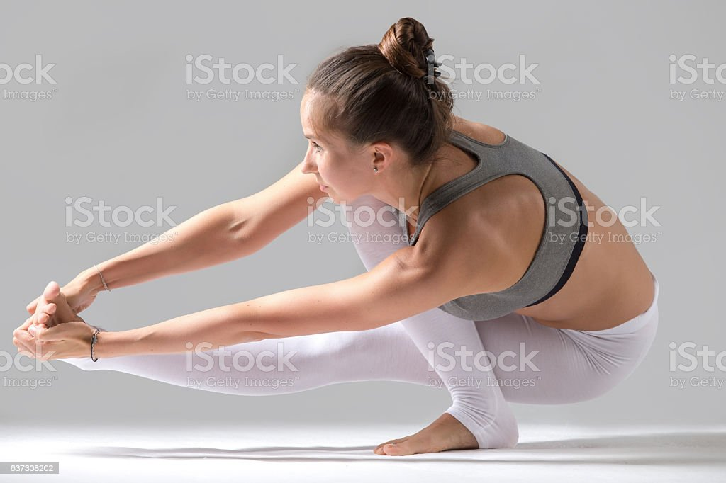 Woman doing Eka Pada Padangusthasana pose with squat stock photo