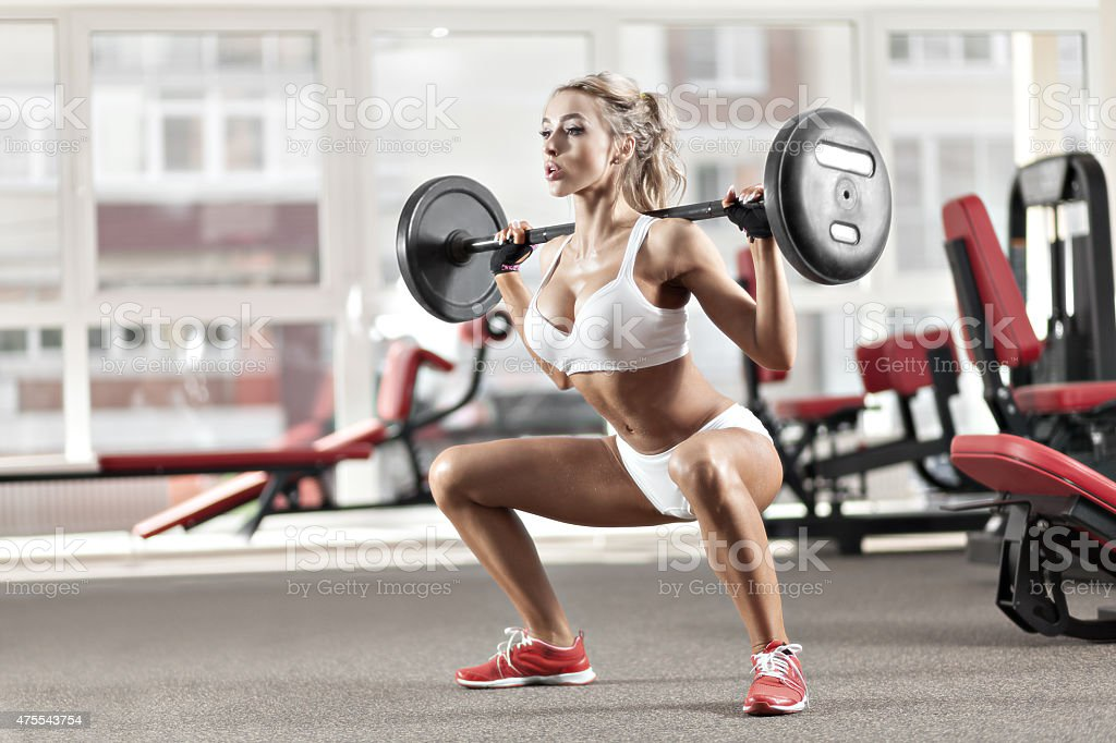 Woman doing exercise with barbell stock photo