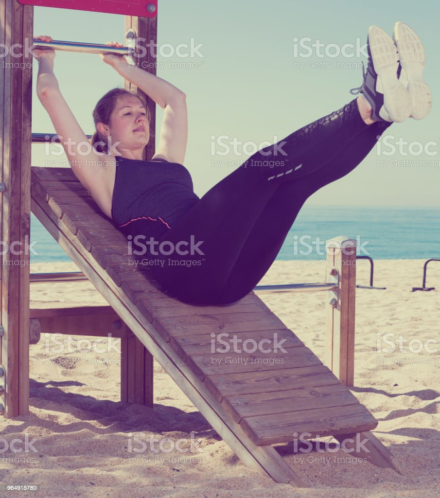 Woman doing exercises on ocean beach royalty-free stock photo