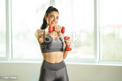 1035512048istockphoto Woman doing exercises with dumbbells at home 1195776389