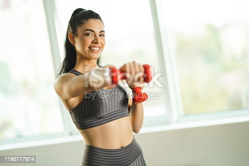 1035512048istockphoto Woman doing exercises with dumbbells 1195777974