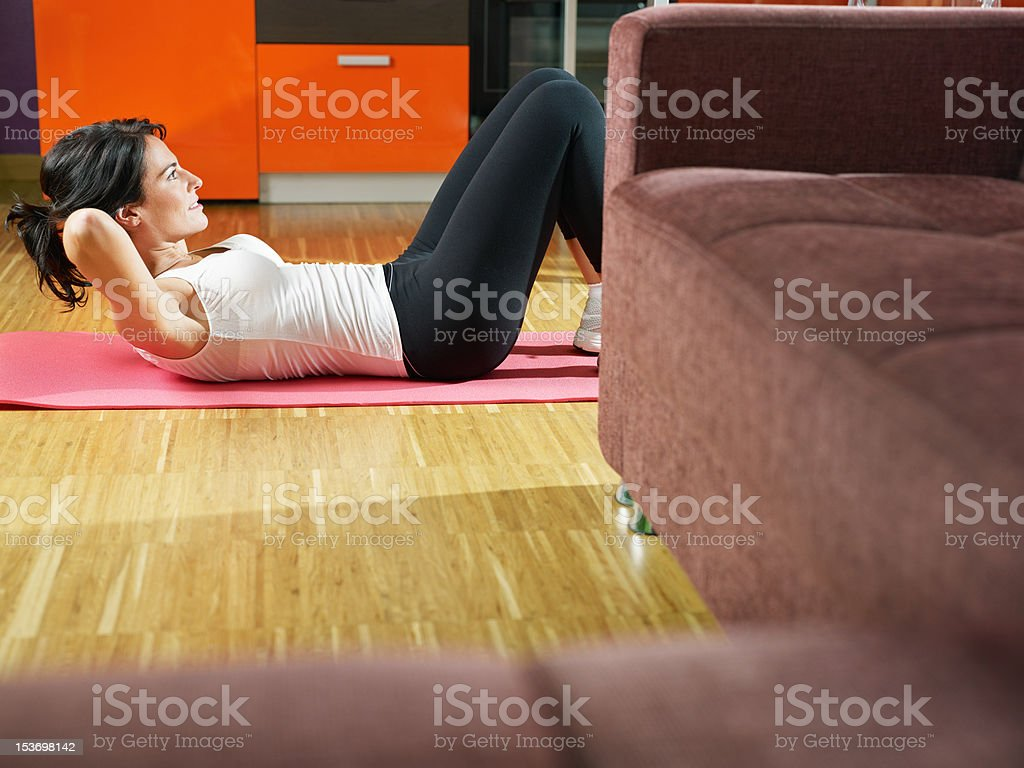 Woman doing exercising on a pink mat at home stock photo