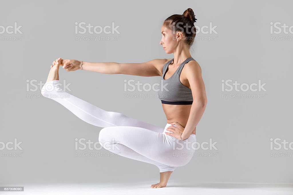 Woman doing Extended Hand to Big Toe pose with squat stock photo