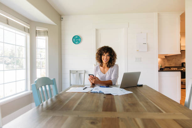 Woman Doing Finances at Home on Smart Phone stock photo
