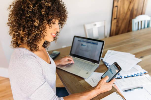 donna che fa finanze a casa sullo smartphone - banca foto e immagini stock