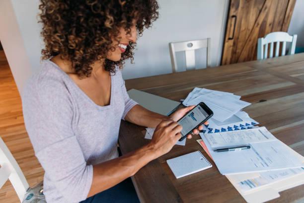 Frau macht Finanzen zu Hause auf Smartphone – Foto