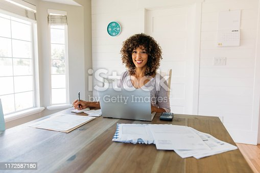 A woman sits at her dining room table with laptop and financial reports doing her monthly budget. She is smiling at the camera as she works on her computer to do monthly finances, pay taxes and save money for the future.