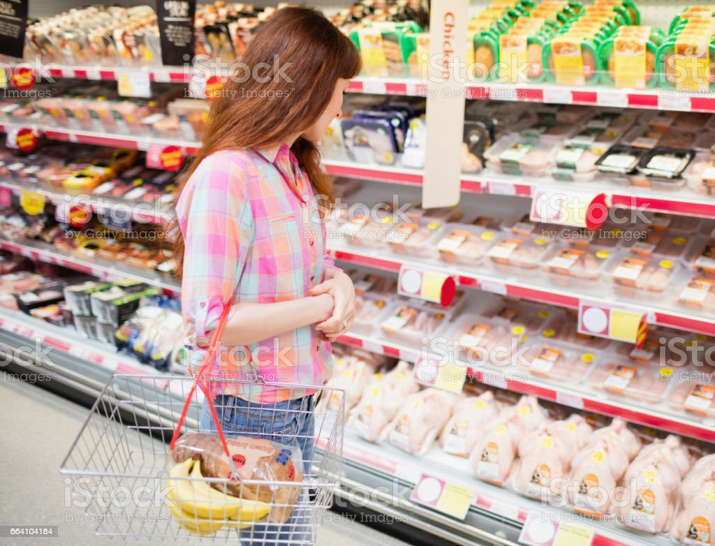 A woman doing grocery shopping with shopping basket foto stock royalty-free