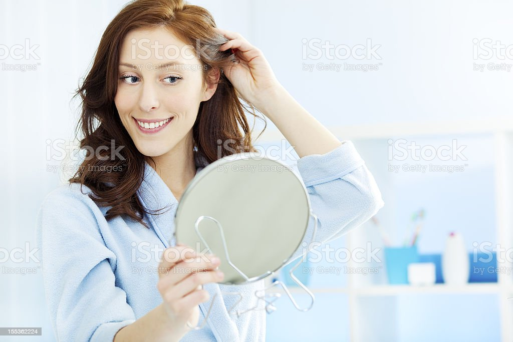 Woman Doing Hairdress in Bathroom stock photo