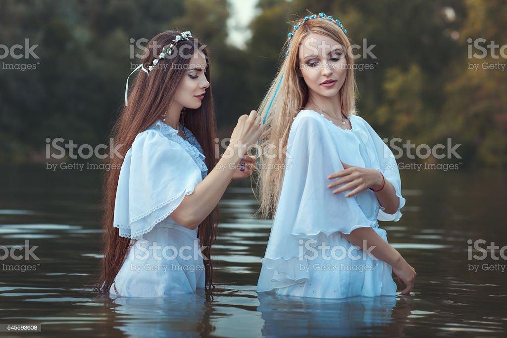 Woman doing hairstyle girlfriend. stock photo