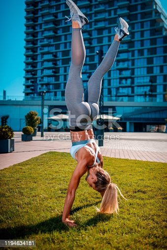 Young woman in sports clothes doing handstand on the lawn between buildings