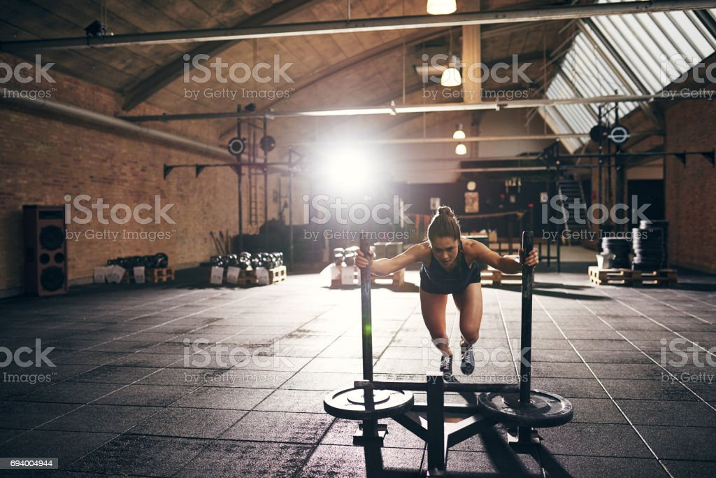 Woman doing hard push-up exercise in gym stock photo
