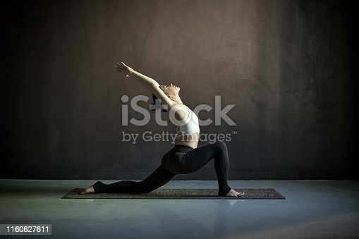 Woman doing hatha yoga asana Anjaneyasana or low crescent lunge pose. Studio shot on black wall full length