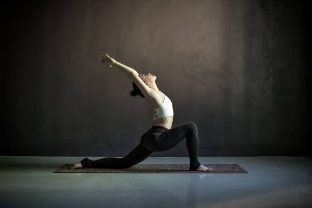Woman doing hatha yoga asana Anjaneyasana or low crescent lunge pose stock photo
