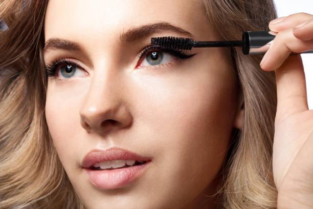 frau tut ihr make-up wimpern mascara schwarz - blaues augen make up stock-fotos und bilder