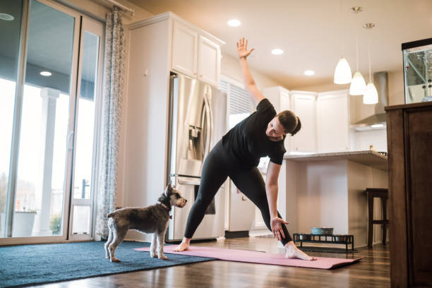 Woman Doing Home Fitness Exercises With Her Dog A mature adult woman does yoga and strength training exercises on a mat in her living room, her pet terrier dog keeping her company and trying to play. exercising stock pictures, royalty-free photos & images