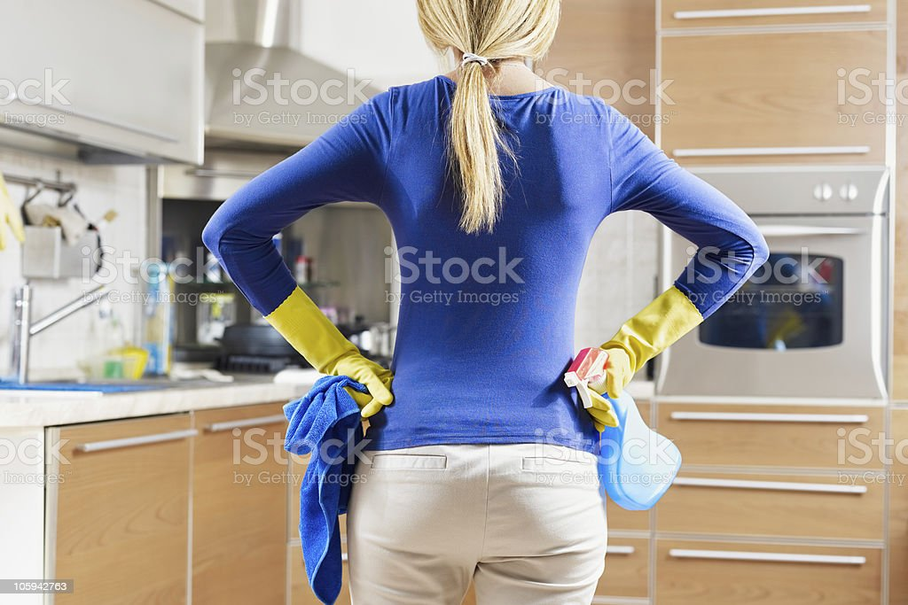 woman doing housekeeping rear view of woman with yellow gloves in kitchen doing housework 25-29 Years Stock Photo