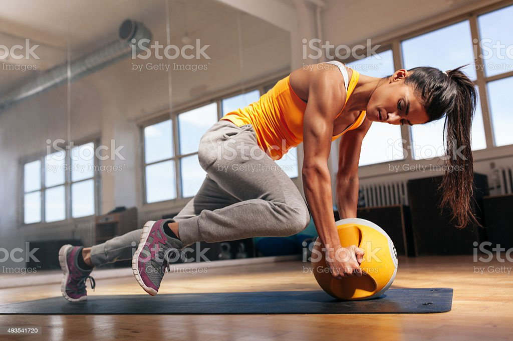 Woman doing intense core workout in gym stock photo