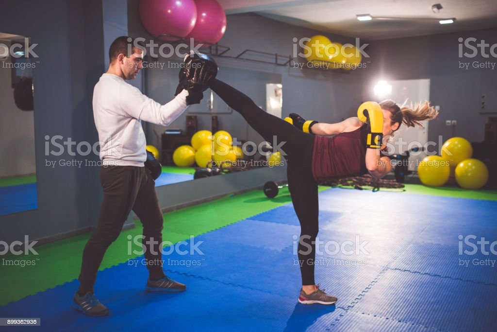 Woman doing kickboxing workout with her coach stock photo